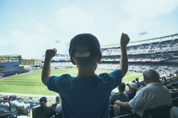 街コンレポート_男の子がスタジアムで野球観戦をしてガッツポーズしています