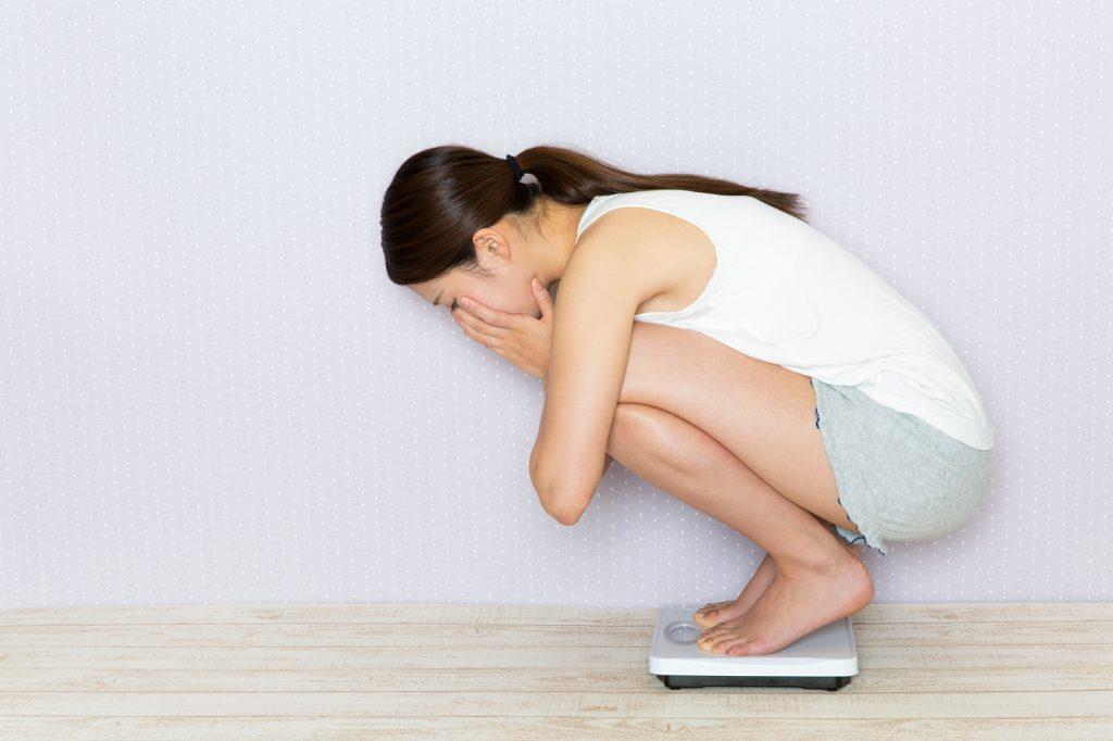 街コンレポート_女性が体重計に乗ってショックを受けています