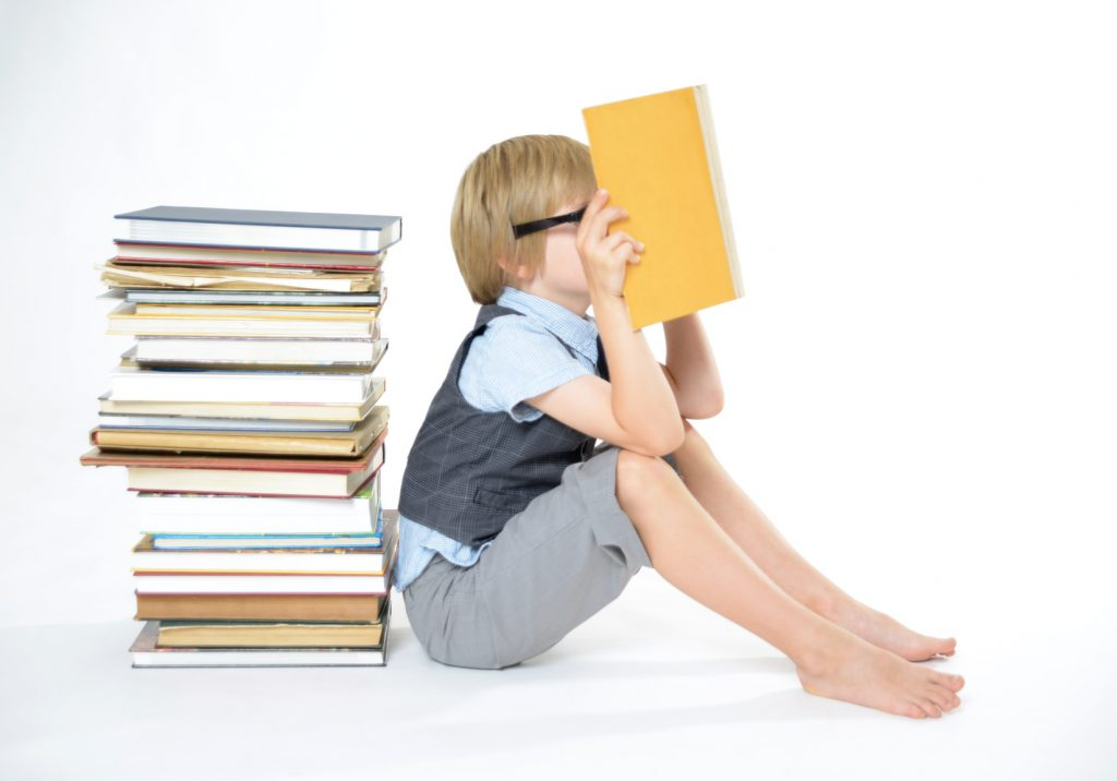 街コンレポート_男の子が沢山の本の前で読書しています