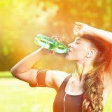 街コンレポート_女性がイヤホンをしてランニング後に水を飲んでいます