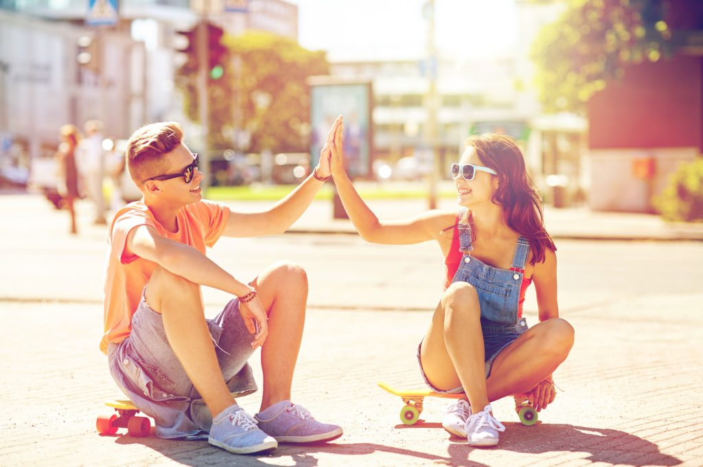 街コンレポート_若い男女がスケートボードに座ってハイタッチしています