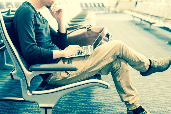 街コンレポート_足を組んでベンチに座りPCを触っている男性