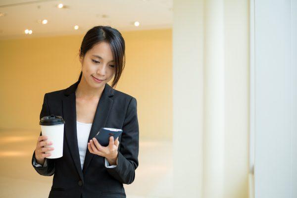街コンレポート_スーツを着た女性が携帯電話を見ています
