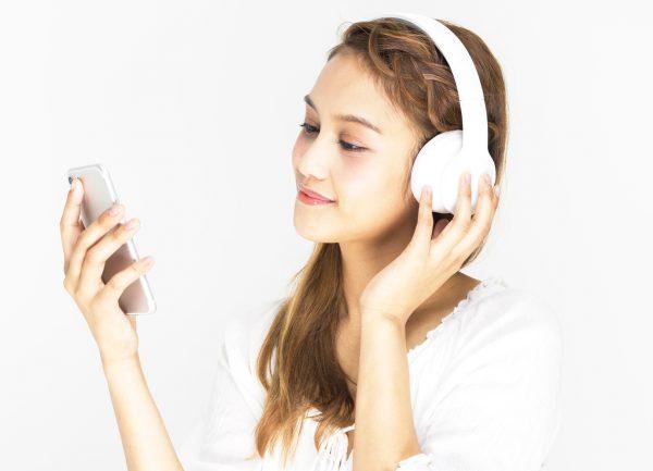 街コンレポート_女性がヘッドフォンをしながら携帯電話を見ています