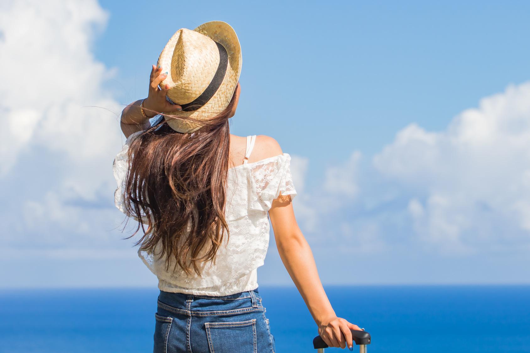 街コンレポート_海で麦わら帽子を抑えて遠くを見つめる女性