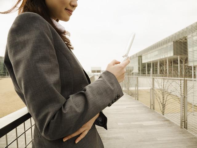 街コンレポート_スーツを着て掲載を操作している女性
