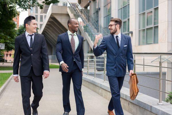 街コンレポート_スーツを着た3人の男性が会話をしながら歩いています
