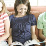 街コンレポート_外国人に囲まれて本を読んでいる日本人女性