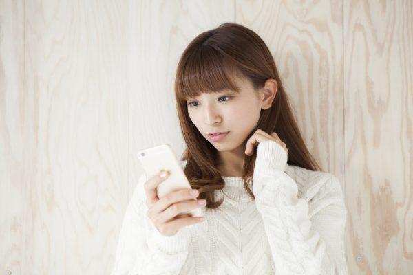 街コンレポート_携帯を見ながら考え事をしている女性