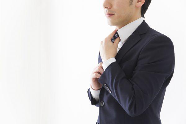 街コンレポート_スーツの男性がネクタイを締め直している