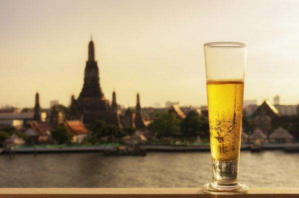 街コンレポート_ロンググラスに入ったビールがバンコクのワットアルンを背景に置いてあります