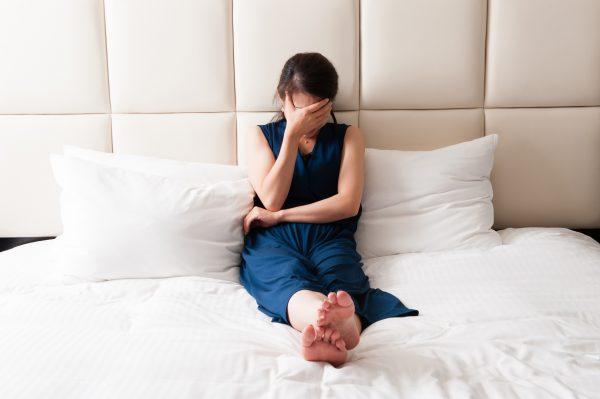 街コンレポート_ベッドの上で頭を抱えている女性