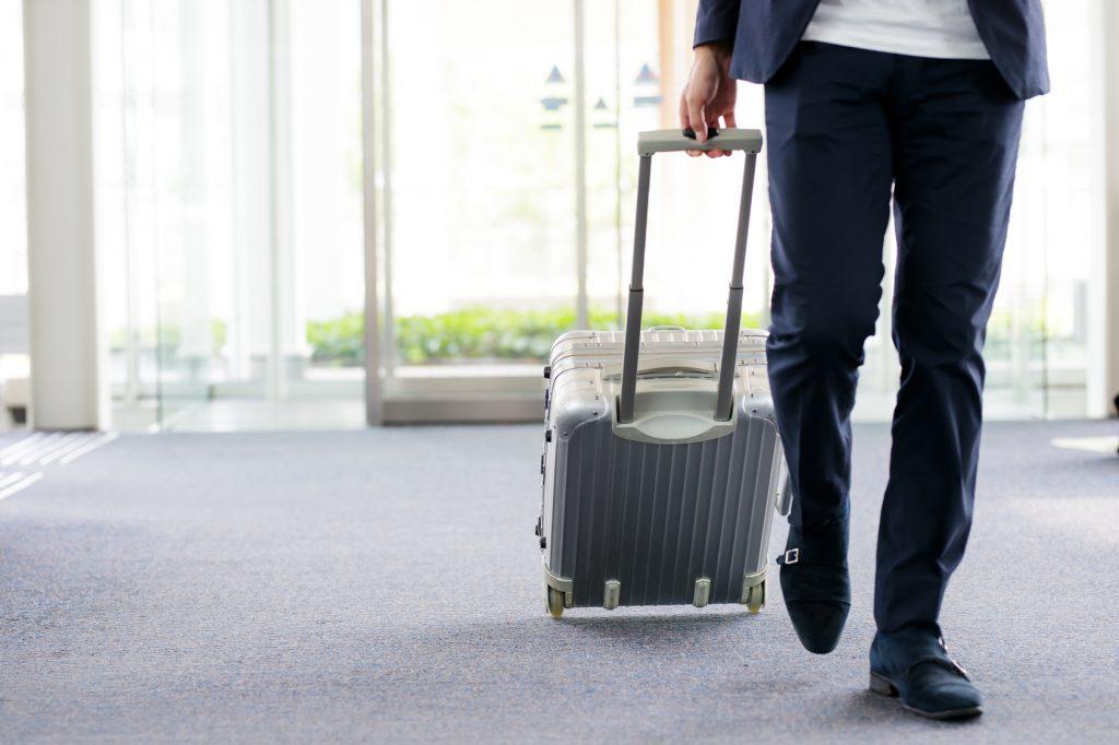 街コンレポート_男性がスーツケースを引いています