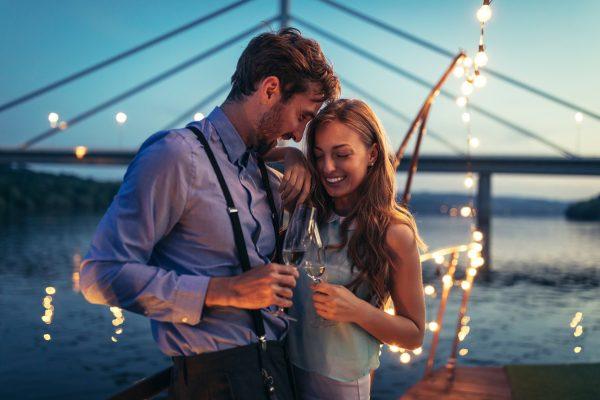 街コンレポート_海辺で寄り添ってシャンパンを飲んでいるカップル