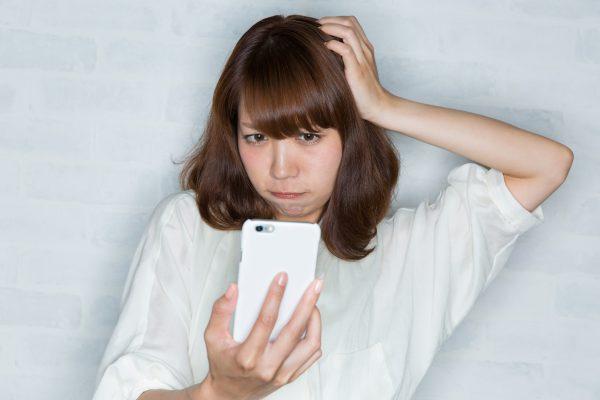 街コンレポート_携帯電話を見ながら頭を抱えている女性