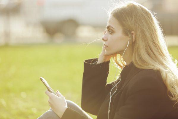 街コンレポート_女性がイヤホンで音楽を聞いています