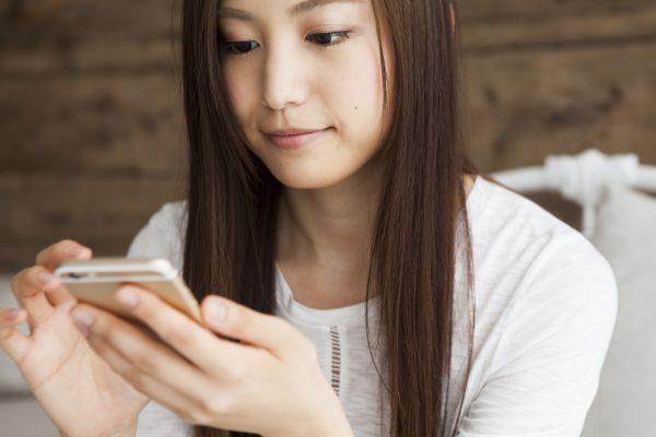街コンレポート_女性が携帯電話を眺めています